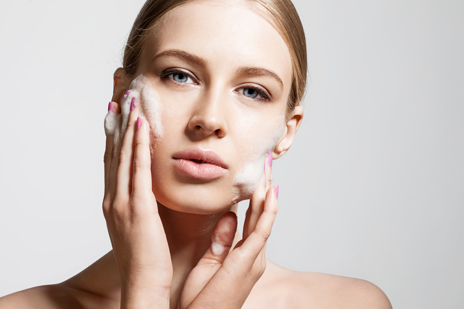 Woman clears a face with skin foam