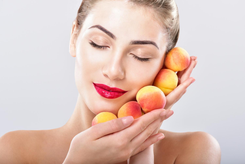 Beautiful woman holding a juicy apricot
